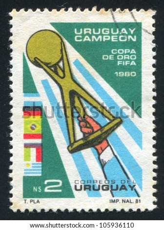URUGUAY - CIRCA 1981: A stamp printed by Uruguay, shows Hand Holding Gold Cup, circa 1981 - stock photo