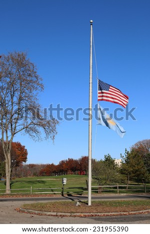 US American and Bergen County, NJ Flags at Half Mast Waving in the Wind with the Beautiful Blue Sky in Background. - stock photo