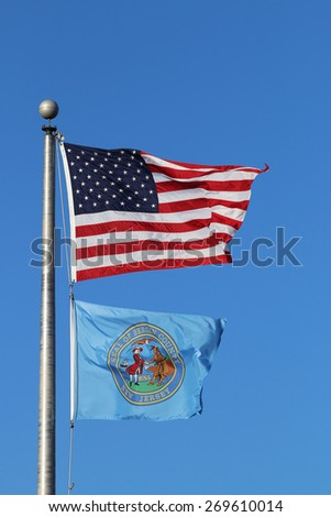 US American and Bergen County, NJ Flags Waving in the Wind with the Beautiful Blue Sky in Background. - stock photo
