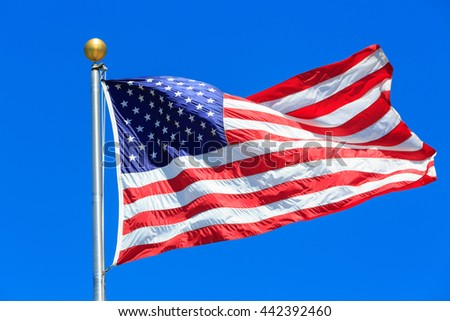 US American flag waving in the wind with a blue sky in background