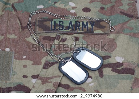 us army camouflaged uniform with blank dog tags - stock photo