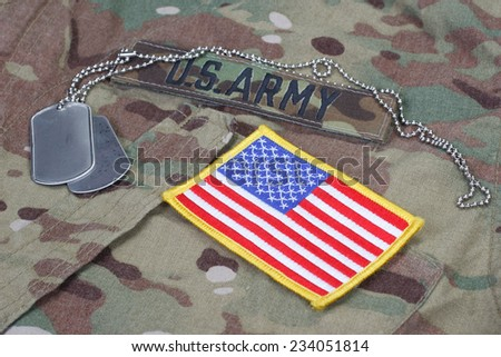 us army camouflaged uniform with US flag patch and blank dog tags - stock photo