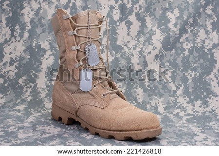 US ARMY concept  - camouflage background with desert boots - stock photo