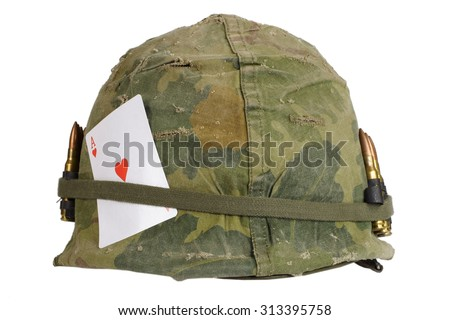 US Army helmet Vietnam war period with camouflage cover and ammo belt and amulet - ace of hearts playing card - stock photo