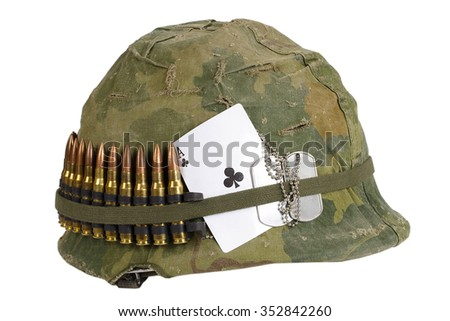 US Army helmet Vietnam war period with camouflage cover and ammo belt, dog tag and amulet - ace of clubs playing card - stock photo