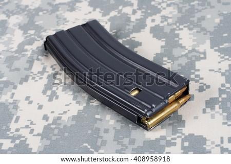 US ARMY M-16 rifle magazine with cartridges on camouflage uniform background - stock photo