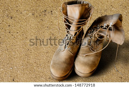 US Army uniform boots on sandy background (war concept) - stock photo