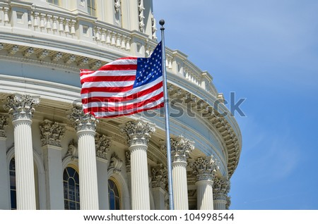 US Capitol Building dome detail with flapping US flag - Washington DC United States - stock photo