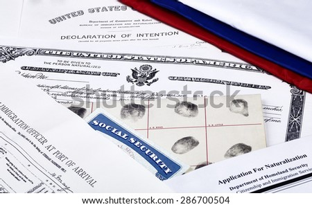 US Certificate of Citizenship, declaration of intention, fingerpirnt card, social security card, application for naturalization and port of arrival manifest with red, white and blue ribbon - stock photo