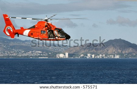 US Coast Guard helicopter flying past Diamond Head crater on island of Oahu, Hawaii. - stock photo