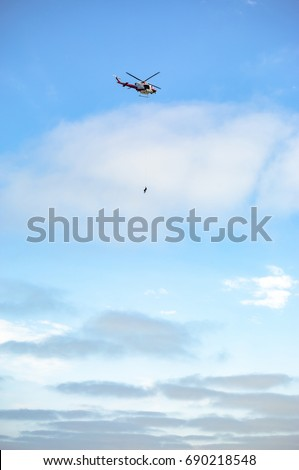 US coastguard helicopter in flight with the sky in the background. US coastguard helicopter in flight with a person hanging after someone fell off a cliff