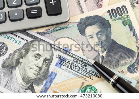 US Dollar and Japanese Yen banknote money with pen and calculator