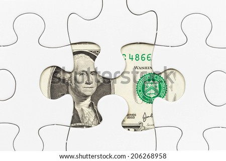 US dollar banknote hidden under puzzle financial concept - stock photo