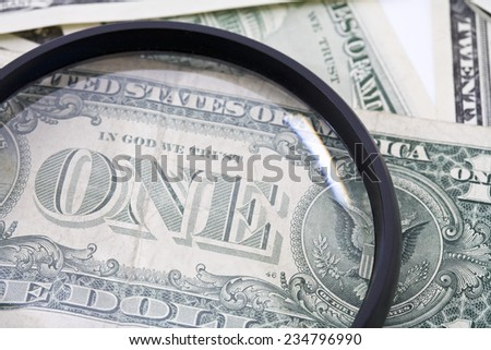 US Dollar bills seen through magnifying glass, close up - stock photo