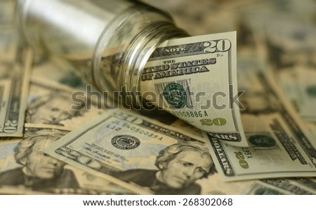 US dollar 20 coming out of glass jar in focus and other 20 dollar bills in soft focus - stock photo