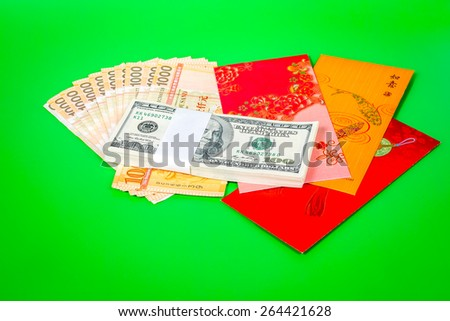US dollar, one hundred dollar notes and Singapore dollars with red envelope on a green background - stock photo