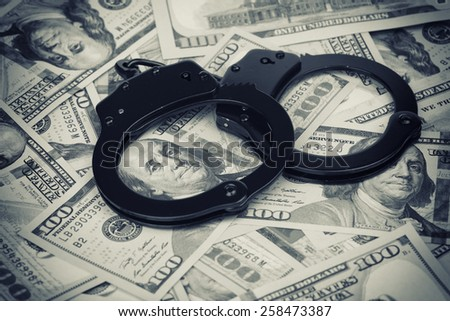 US dollars. Handcuffs on money close up