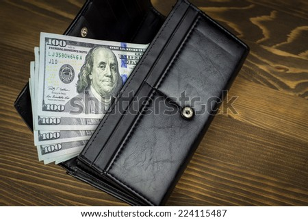 US dollars in wallet. Wood background
