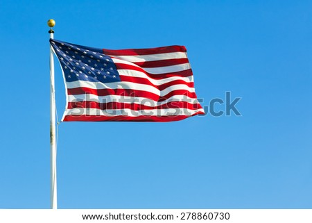 US flag against blue sky - stock photo