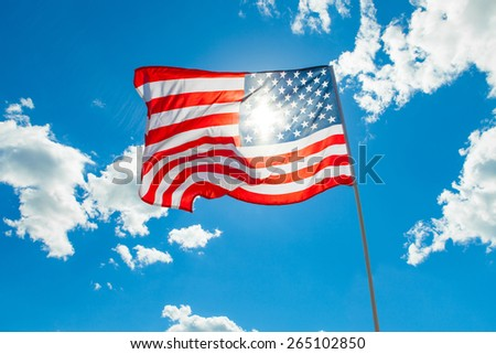 US flag and cumulus clouds on background - stock photo