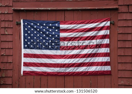US Flag displayed on red barn door on Memorial Day, 2011, outside of Lexington, MA - stock photo