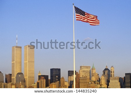 US Flag flying over skyline of New York City from New York Harbor, NY - stock photo