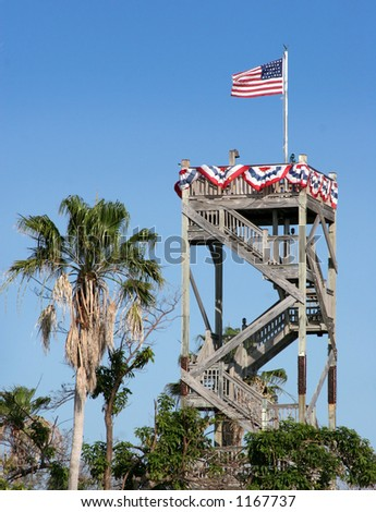 US flag on top of a tower decorated in red, white and blue.