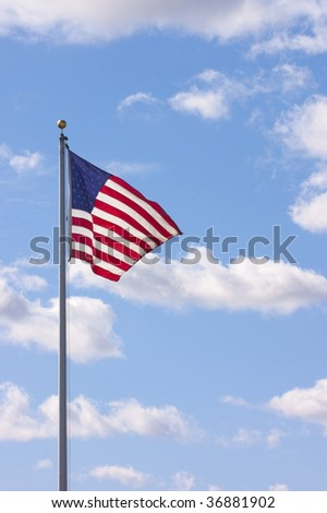 US flag waving with clouds in the sky
