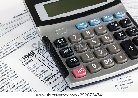 US Individual Tax Return Form 1040 close up with calculator. - stock photo
