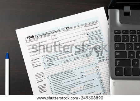US Individual Tax Return Form 1040 on a table next to laptop computer - stock photo