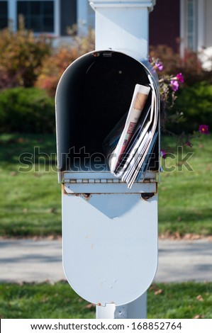US Mail box with newspaper and letters in front of a house - stock photo