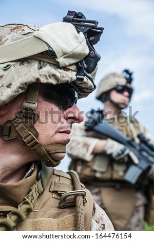 US marine half-turned to the camera. His brother-soldier looking in the same direction - stock photo