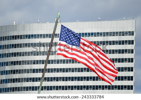 US National flag with corporate skyscraper building background - stock photo