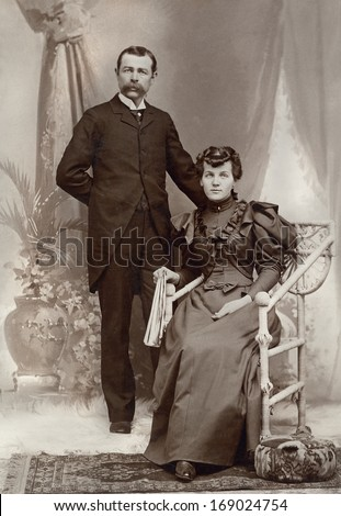 US - NEW YORK - CIRCA 1895 - A vintage antique photo of a young couple. The husband is standing while his wife is sitting in a chair. A photo is from the Victorian era. CIRCA 1895 - stock photo