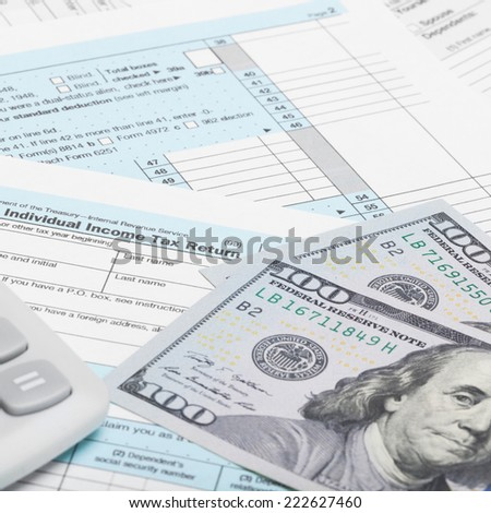 US of America Tax Form 1040 with calculator and dollars - 1 to 1 ratio - stock photo