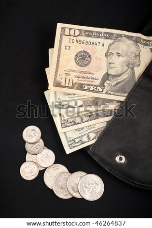 US Paper Currency in Wallet with Scattered Coins on Black - stock photo
