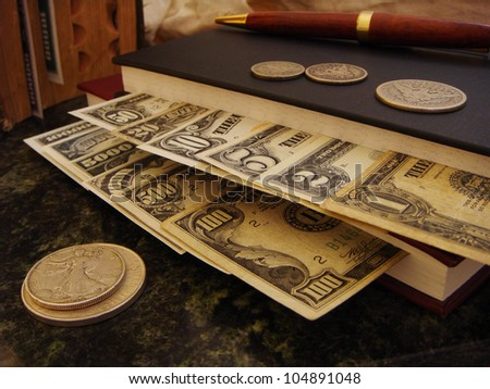 US Paper Money Organized within Money Management Books with Silver Coins along with an Elegant Wooden Pen, Money Peeking out of Old Book and Money Canvas Bag in Background