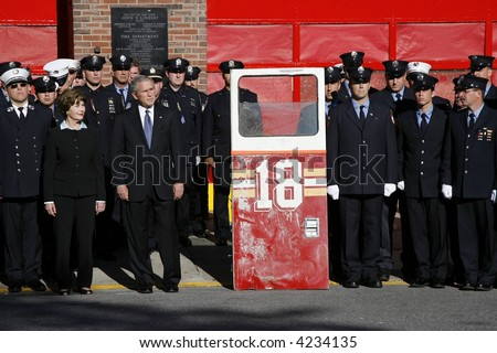 US President George W. Bush with First Lady Laura Bush standing next to a fire engine door - stock photo