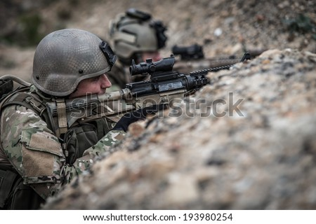 us rangers hidden in trench, during battle - stock photo