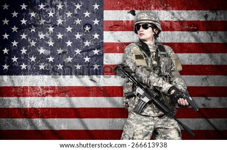 US soldier holding rifle on a american flag background - stock photo