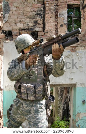 US Soldier on urban patrol mission aiming his rifle - stock photo