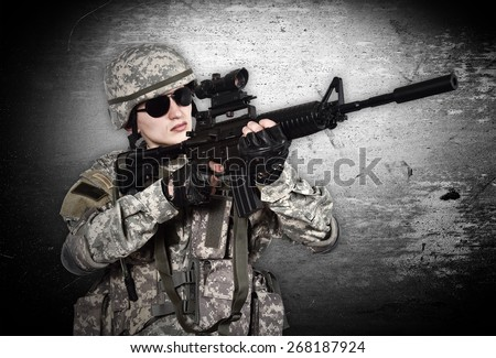 US soldier with rifle on a gray background - stock photo