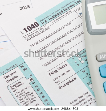 US 1040 Tax Form and calculator over it - studio shot