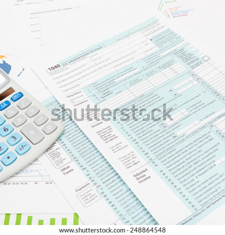US 1040 Tax Form and calculator - studio shot - stock photo