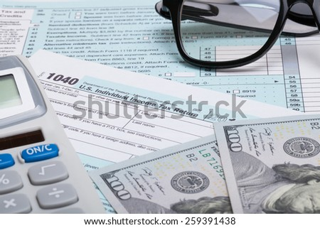 US 1040 Tax Form, calculator, glasses and dollars - studio shot - stock photo