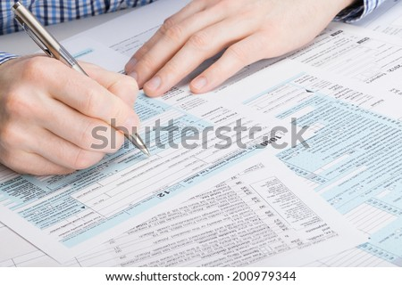US 1040 Tax Form - male filling out tax form - stock photo