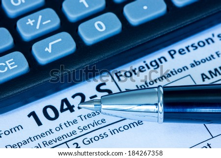 US tax form 1042-S with pen and calculator - stock photo