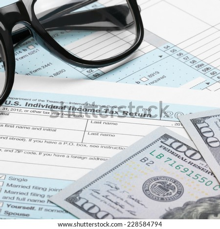 US Tax Form 1040 with dollars and glasses - stock photo