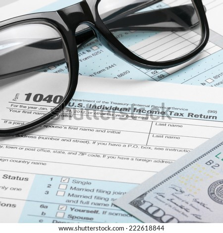 US Tax Form 1040 with dollars and glasses - 1 to 1 ratio - stock photo