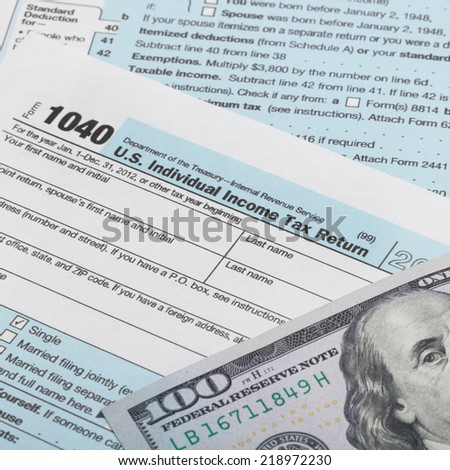 US Tax Form 1040 with 100 dollars banknote above it - 1 to 1 ratio